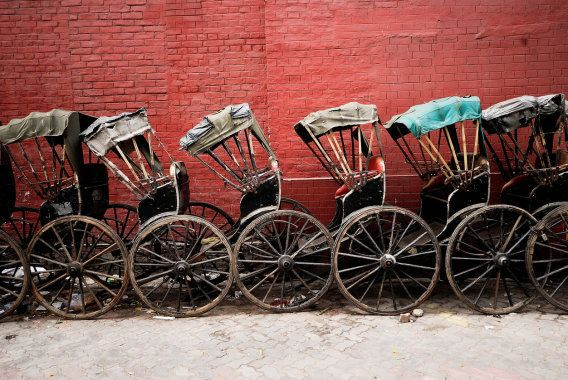 Hand pulled rickshaws against red wall in