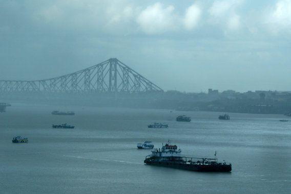 A passenger boat moves along the Hooghly river after passing under the Howrah bridge during a monsoon...