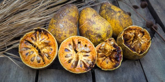 advantage of bael fruit or quince as fruit, medicine, glue on wooden background
