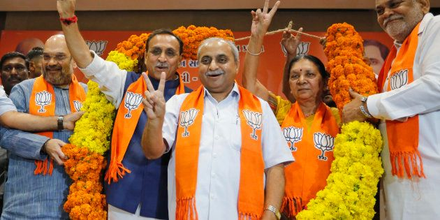 Vijay Rupani, second left, state president of Bharatiya Janata Party (BJP) in Gujarat, is garlanded as...