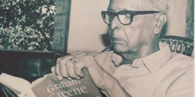 Photograph of a photo of R.K. Narayan reading Graham