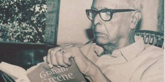Photograph of a photo of R.K. Narayan reading Graham Greene.