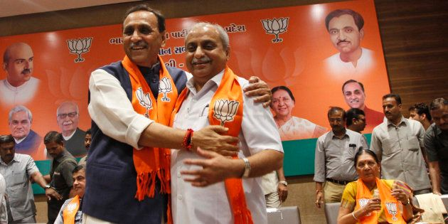 Vijay Rupani, left, state president of Bharatiya Janata Party (BJP) in Gujarat, is congratulated by Nitin...