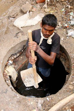 Sanjay Prasad age 33, cleans drains for a living, goes inside a drain with his only tool on July 13, 2012 in New Delhi, India.