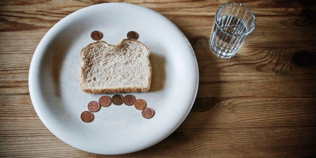 Glass of water and sad face made out of a slice of stale bread and pennies on a white plate