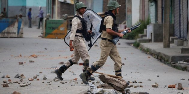Indian policemen chase protesters during a protest in Srinagar against the recent killings in Kashmir,...