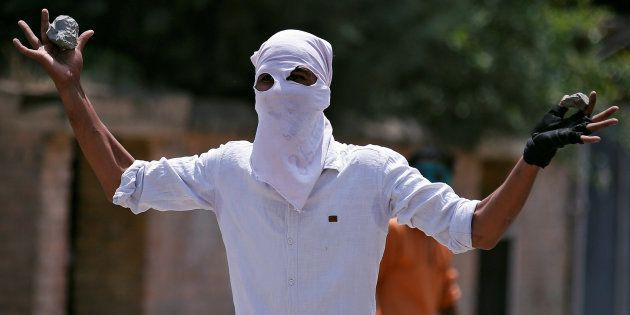A masked protester gestures towards the Indian police during a protest in Srinagar, against the recent...