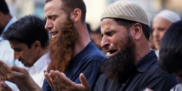 A man cries as others offer prayers on a road as a protest in Srinagar against the recent killings in...