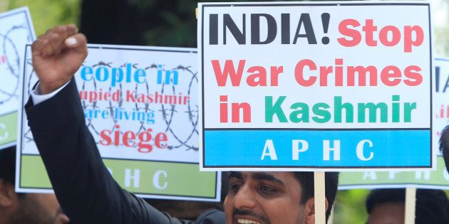 A supporter of All Parties Hurriyat (Freedom) Conference (APHC) chants slogans with others to condemn...