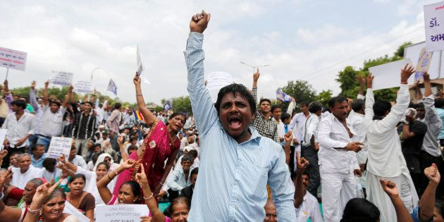 People shout slogans as they attend a protest rally against what they say are attacks on India's Dalit...