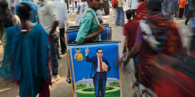 A man holds posters of B.R. Ambedkar for sale on his death anniversary in Mumbai, on 6 December 2011....
