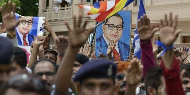 Photographs of Dr Ambedkar are raised as Indian members of the Dalit community take a pledge not to skin...