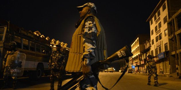 Indian paramilitary troopers patrol during a curfew in Lal Chowk in Srinagar on August 14,