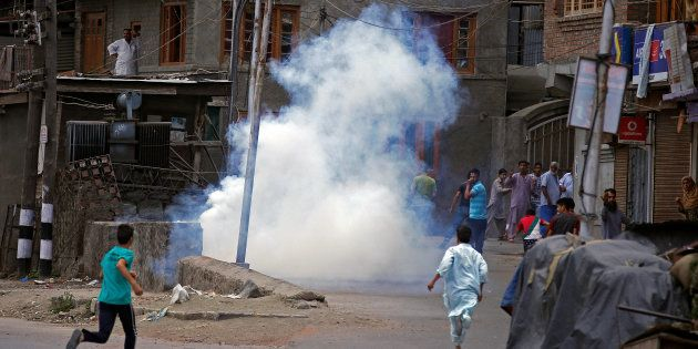 Police (not pictured) fire tear gas during a protest in Srinagar against the recent killings in Kashmir,...