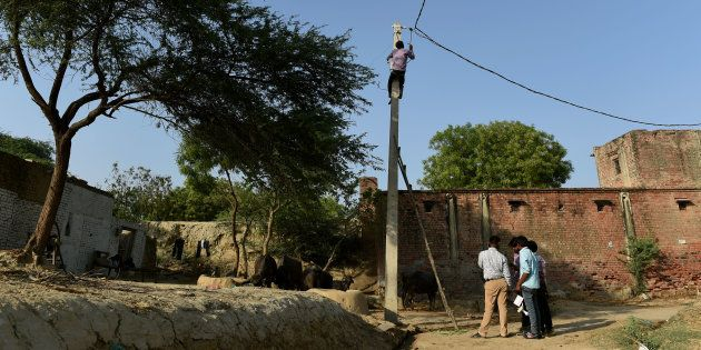 In this photograph taken on 23 April, 2016, an Indian worker climbs up an electricity pole as others...