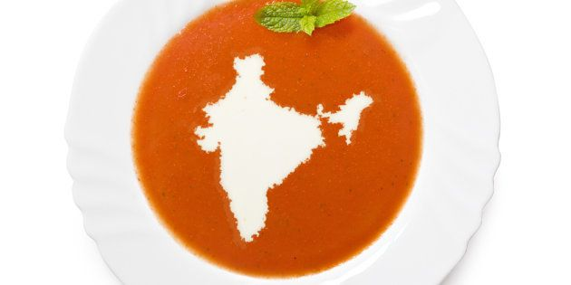 A top shot of an isolated plate with tomatosoup and cream in the shape of India (Asia). (series)