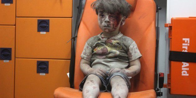 5-year-old Omran Daqneesh sits at the back of an ambulance after he got injured during an airstrike on...