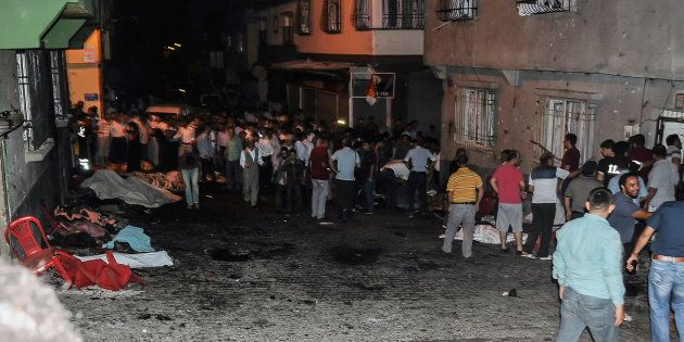 Bodies are covered as people gather at the explosion site on August 20, 2016 in Gaziantep, in a late...