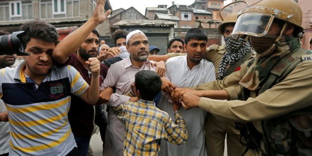 Indian policemen detain Masroor Abbas Ansari (C), leader of the All Parties Hurriyat Conference (APHC)...