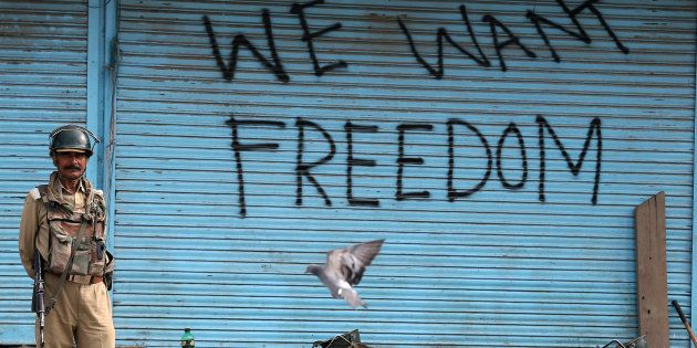 Graffiti is painted on shop shutters in Srinagar after an escalation of violence that officials have...