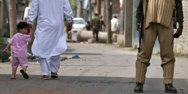 A boy looks back at a member of the security forces in Srinagar as the city remains under curfew following...