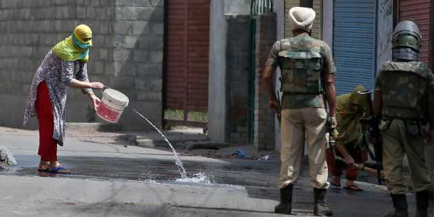 Women wash the street outside their house in Srinagar as security forces patrol during a curfew following...