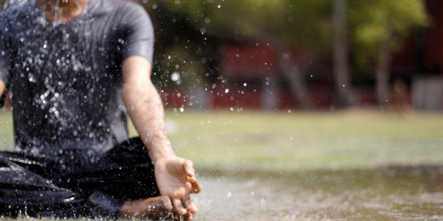 A young man doing yoga in rain. Image has a Low depth of field.