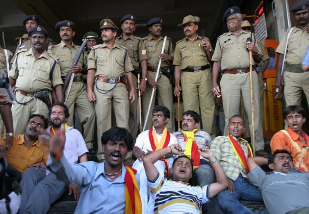 Pro Karnataka activists lie on the ground as they shout slogans to protest against the verdict of Cauvery...