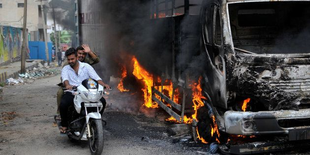 Men ride a motorcycle past a lorry in Bengaluru, which was set on fire by protesters, India September...