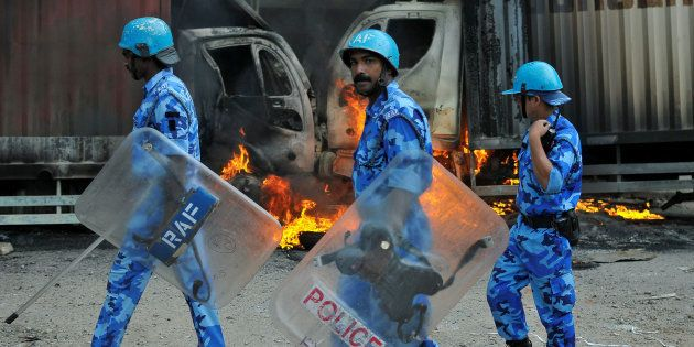 Members of the security forces make their way past burning lorries in Bengaluru, India September 12,