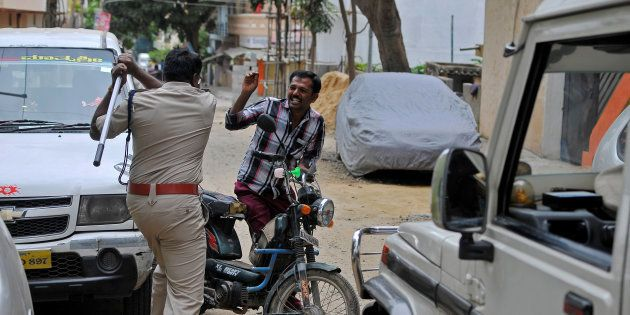 Police raises his baton at a man who defied a curfew in Bengaluru, following violent protests, India...