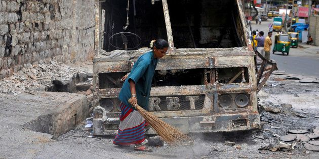 A municipal worker sweeps around the charred remains of a lorry set ablaze during the violent protests...