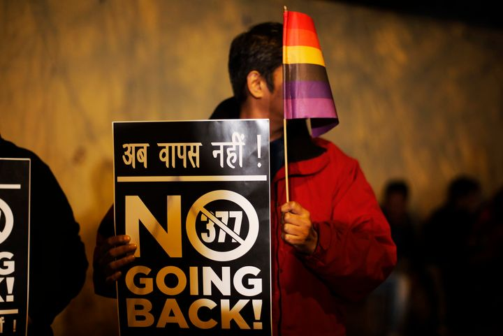 An Indian gay rights activist holds up a placard and a flag during a protest against a recent Supreme Court verdict that upheld section 377 of the IPC