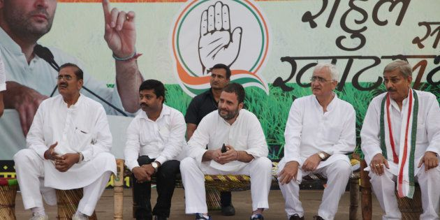 Congress vice president and leader Rahul Gandhi and other party leaders sit on cots during a public meeting...