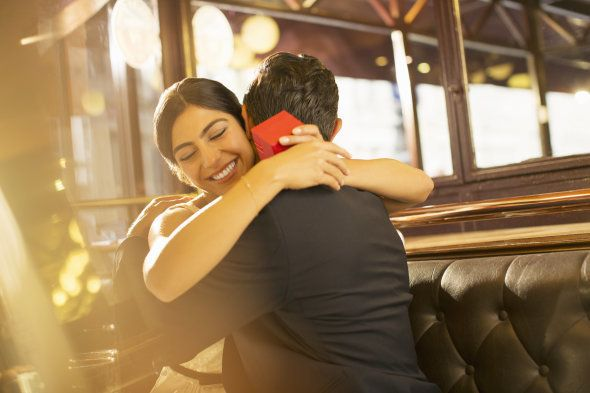 Woman with jewelry box hugging man in restaurant