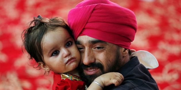 An Afghan Sikh holds his child inside a Gurudwara, during a religious ceremony in Kabul, Afghanistan...