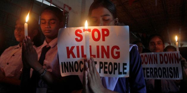 School children hold candles and placards during a vigil for the soldiers who were killed after gunmen...