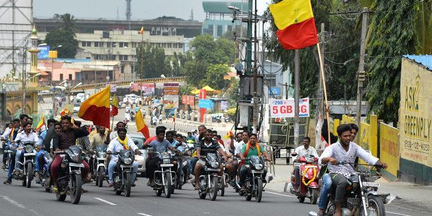 Pro-Karnataka activists wave the Karnataka flag while they participate in a motorcycle rally during a...