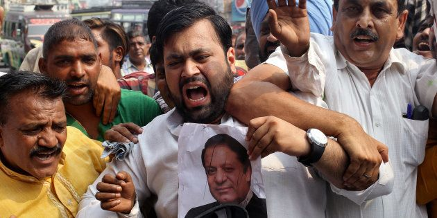 A demonstrator hits a poster of Pakistan's Prime Minister Nawaz Sharif during a protest organised by...
