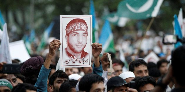 A picture of Hizbul Mujahideen commander Burhan Muzaffar Wani is held up during a rally condemning the...