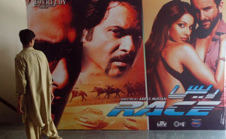 A man walks past an Indian movie poster inside a cinema in Karachi April 21, 2008. Pakistan banned Indian films after going to war with its neighbour in 1965 but over the past few years, as relations between the nuclear-armed rivals have improved, authorities have been allowing a trickle of Indian films to be shown in cinemas. That has delighted movie fans and cinema operators but Pakistani film producers fear a flood of Indian films could mean the end of the local film industry. Picture taken April 21, 2008.  To match feature PAKISTAN-BOLLYWOOD/        REUTERS/Athar Hussain/Files   (PAKISTAN)
