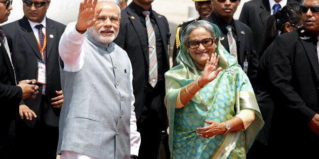 India's Prime Minister Narendra Modi waves with Bangladesh's Prime Minister Sheikh Hasina at Shahjalal...
