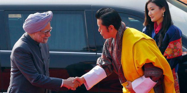 Bhutan's King Jigme Khesar Namgyel Wangchuck shakes hands with India's Prime Minister Manmohan Singh...