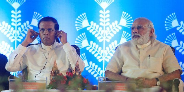 Prime Minister Narendra Modi looks on as Sri Lanka's President Maithripala Sirisena (L) adjusts his earphones...