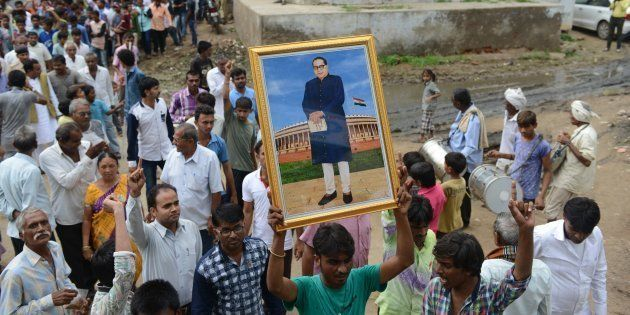 A member of the Dalit community holds up a picture of social reformer Bhimrao Ramji Ambedkar during the...