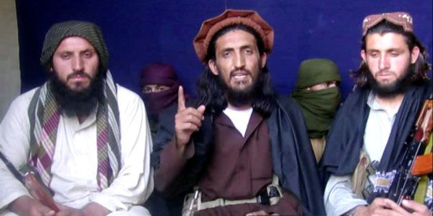 In this file image taken from a video recording, Omar Khalid Khorasani (C), a top Pakistan Taliban commander,...
