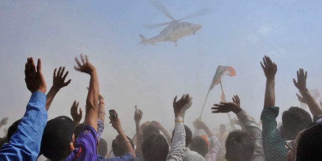 People wave towards a helicopter carrying Narendra Modi in Uttar Pradesh April 21,