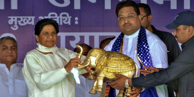 Mayawati (2nd L), chief of Bahujan Samaj Party (BSP), receives a model of an elephant, the BSP's electoral...