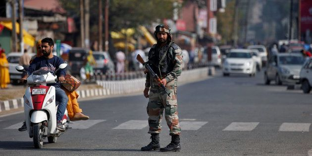 An Indian army soldier stands guard on a road on the outskirts of Srinagar, October 3,