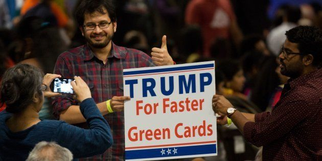 A sign suggesting Republican presidential candidate Donald Trump supports expediting work visas is seen...